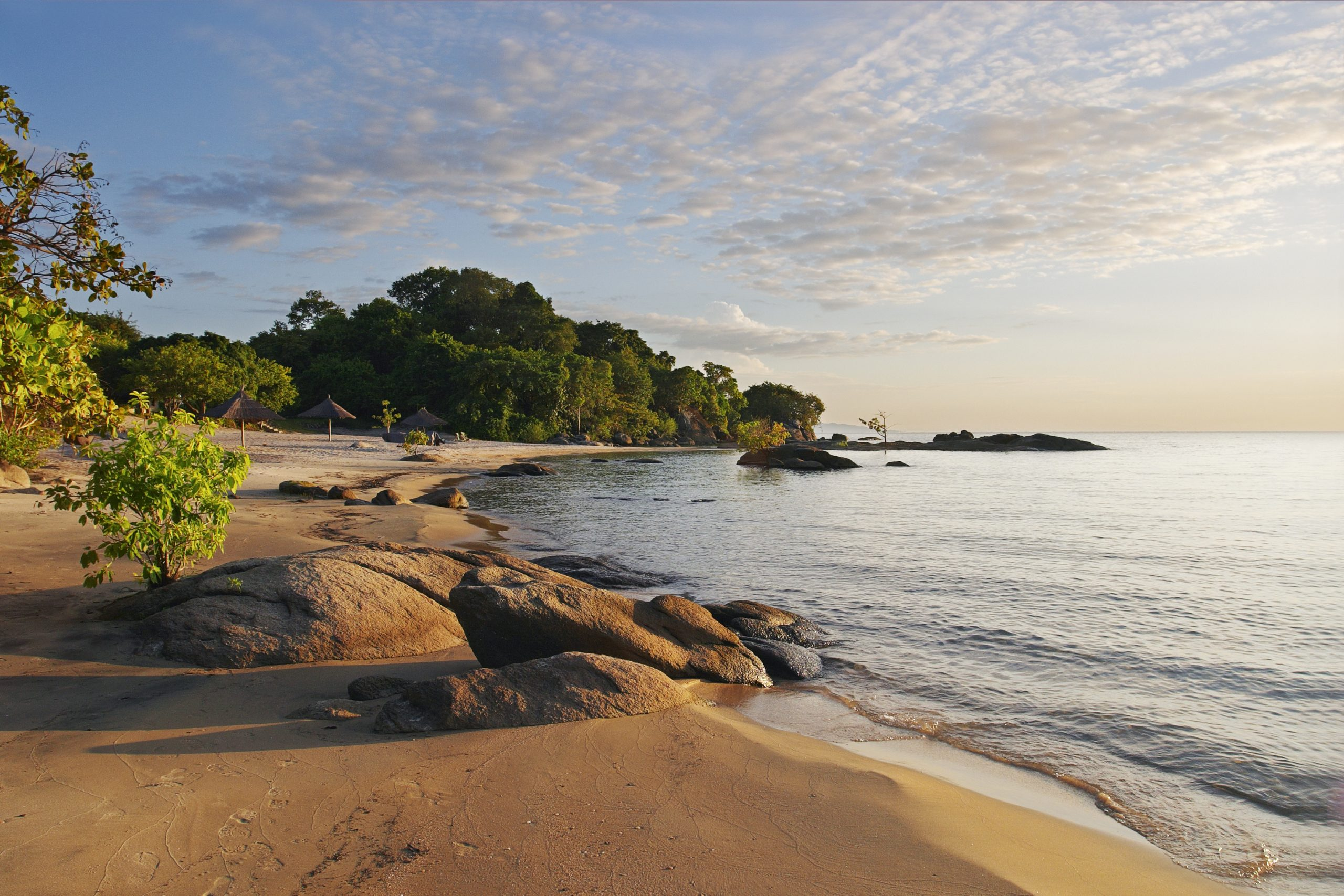 Makuzi Beach, Lake Malawi, just after sunrise. The early morning light is throwing long shadows on the beach.