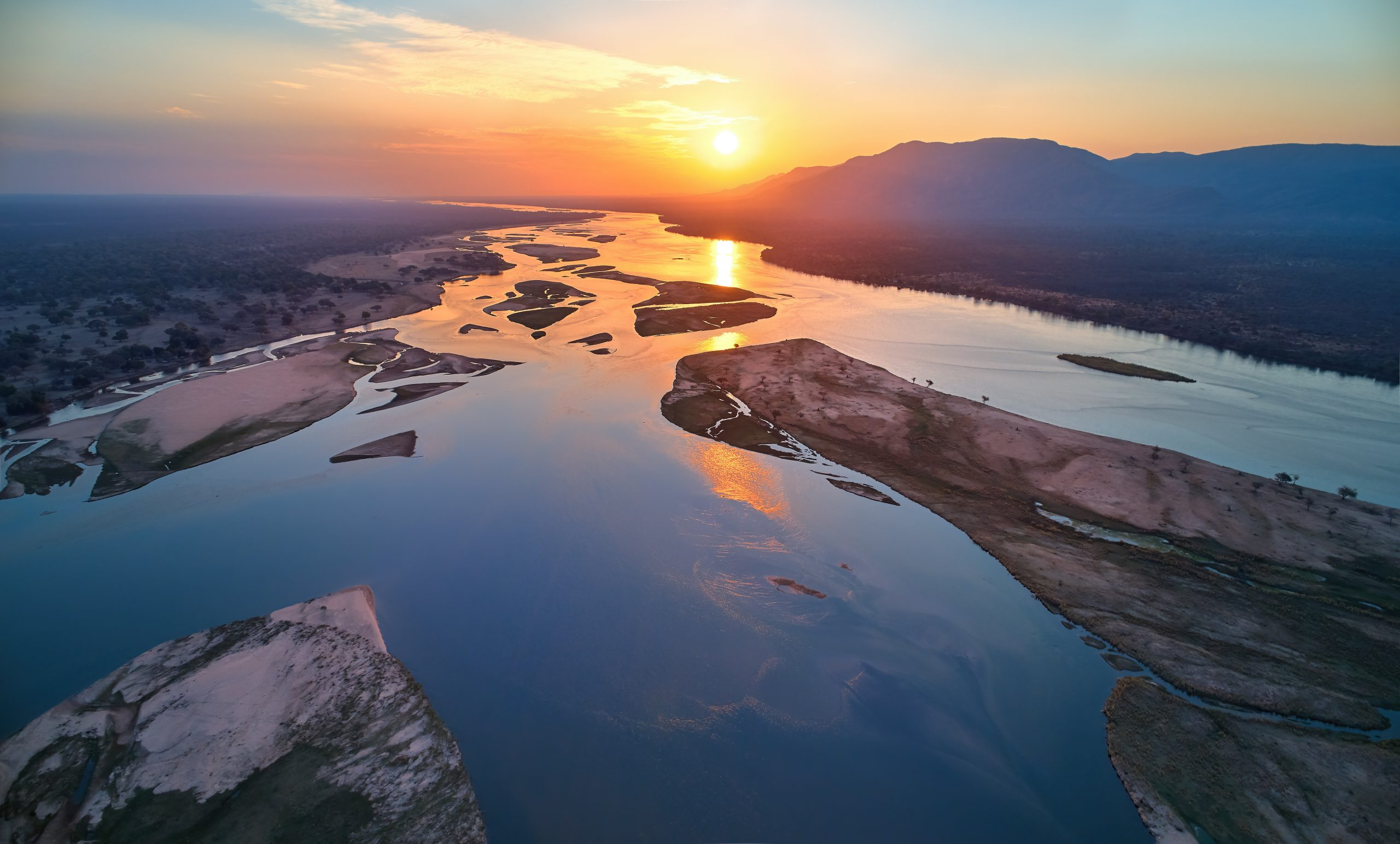 Aerial, west view of Zambezi river, mountains and african wilderness. Colorful sunset reflecting on huge  Zambezi river, view from above. UNESCO heritage site, Mana Pools national park, Zimbabwe.